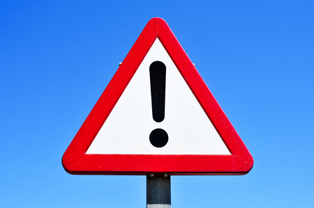 attention sign: a triangular traffic sign with an exclamation mark against the blue sky