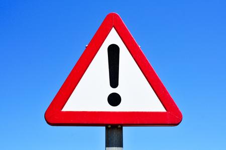 trójkątny znak drogowy z wykrzyknikiem na tle błękitnego nieba