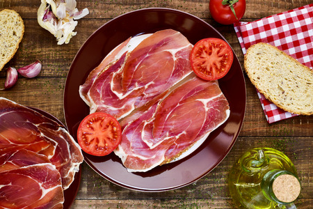 high-angle shot of a plate with spanish pan con tomate y jamon, sliced bread topped with tomato and serrano ham and dressed with olive oil, on a rustic wooden table