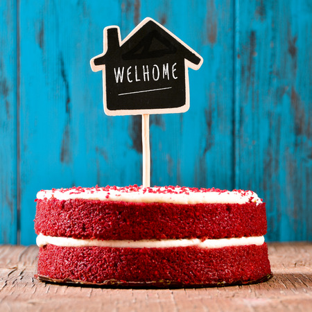 a red velvet cake with a chalkboard in the shape of a house with the text welhome, like welcome home, on a rustic wooden surface