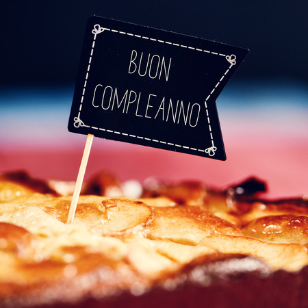 buon: closeup of a black flag-shaped signboard with the text buon compleanno, happy birthday in italian topping a cake