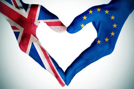 position d amour: les mains d'une jeune femme � motifs avec le drapeau du Royaume-Uni et la Communaut� europ�enne formant un coeur, avec une vignette ajout� Banque d'images