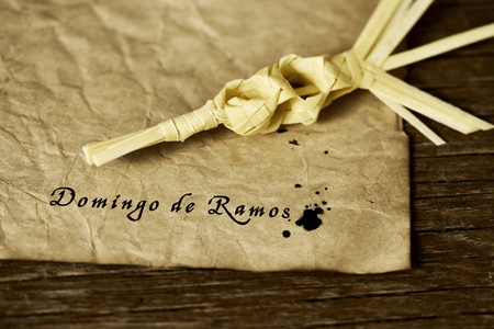 sunday: a traditional spanish braided palm to be blessed on Palm Sunday and the text Domingo de Ramos, Palm Sunday in spanish written with ink in a yellowish paper, placed on a rustic wooden surface Stock Photo