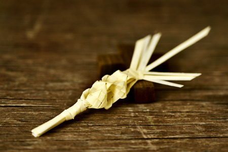 christianity palm sunday: a traditional spanish braided palm to be blessed on Palm Sunday and a small wooden cross on a rustic wooden surface