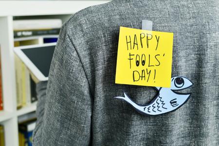attach: primer plano de un hombre joven con un pez de papel y una nota con el día feliz de los inocentes de texto adjunto con cinta a la espalda