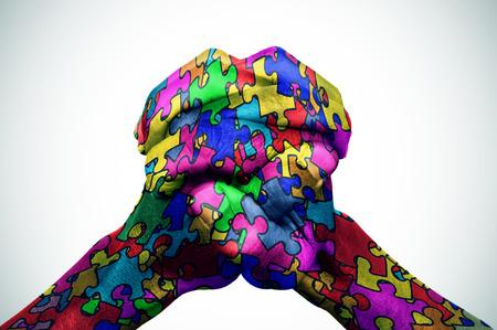 Mann, die Hände mit vielen Puzzleteile in verschiedenen Farben, Symbol des Autismus Bewusstsein, mit einer leichten Vignette zusammengestellt, hinzugefügt gemustert Standard-Bild - 54039116