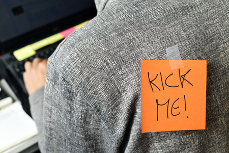 closeup of a young man with a paper with the text kick me attached to his back Standard-Bild