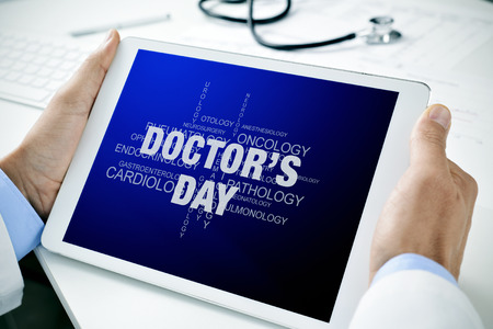 doc: closeup of a doctor man sitting at his office desk holding a tablet computer with a tag cloud of different medical specialties and the text doctors day in its screen