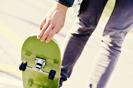 generation y: closeup of a young caucasian man skateboarding on a non-traffic street
