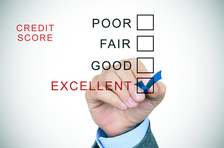 credit risk: closeup of the hand of a man in suit marking excellent from a list of the different ranges of the credit score: excellent, good, fair and poor