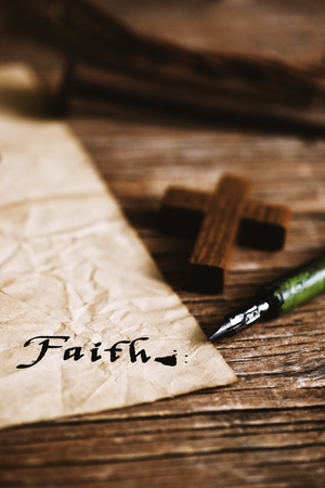 crucify: closeup of a small wooden christian cross, an old dip pen and a yellowish paper with the word faith written with black ink in it, on a rustic wooden table