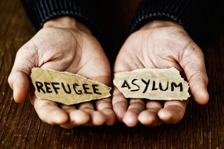 foreign policy: closeup of the hands of a young man with two pieces of paper with the words refugee and asylum written in each one, with a dramatic effect Stock Photo