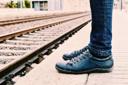 despedida: Primer plano de los pies de un hombre joven que llevaba pantalones vaqueros que está esperando el tren en el andén de la estación de tren Foto de archivo
