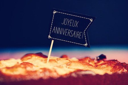 joyeux: closeup of a black flag-shaped signboard with the text joyeux anniversaire, happy birthday in french topping a cake