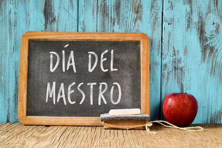 テキスト ダイヤ ・ デル ・ マエストロと黒板、チョーク、消しゴム、レトロな効果を持つ素朴な木製のテーブルに赤いリンゴの作品、スペイン語で