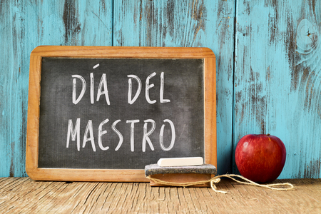 maestro: a chalkboard with the text dia del maestro, teachers day written in Spanish, a piece of chalk, an eraser and a red apple on a rustic wooden table, with a retro effect
