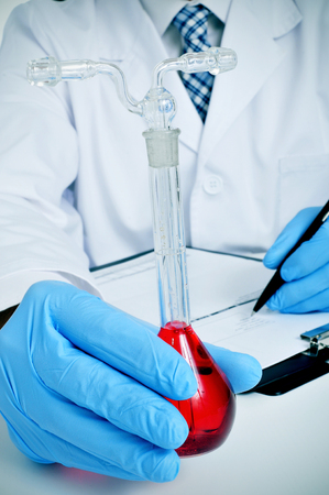 volumetric flask: closeup of a young caucasian man in white coat with a volumetric flask with a red liquid in his hand in a laboratory Stock Photo