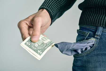 impoverish: a young caucasian man in jeans taking one US dollar out of his pocket