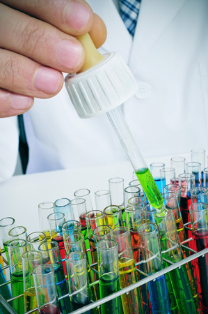assays: closeup of a young caucasian man in white coat with a dropper in his hand and some test tubes with liquids of different colors in a laboratory