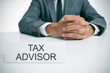 tax consultants: a man wearing a gray suit sitting at his office desk with a signboard in front of him with the text tax advisor written in it Stock Photo