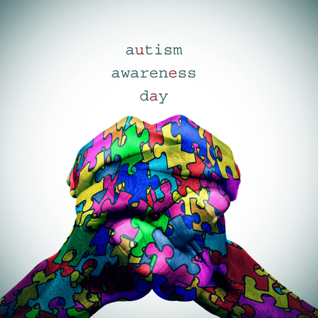 developmental disorder: text autism awareness day and the hands of a man put together patterned with many puzzle pieces of different colors, with a slight vignette added