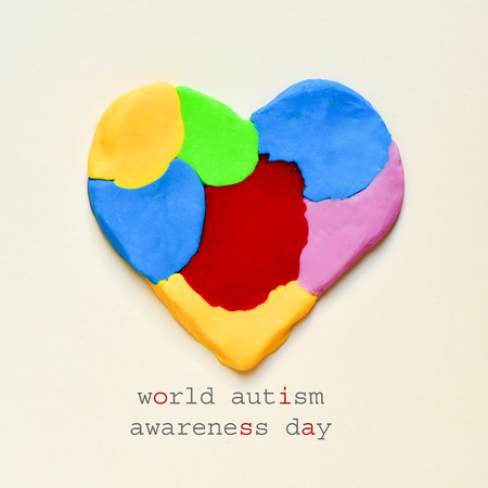 developmental disorder: the text world autism awareness day and a heart made from modelling clay of different colors on an off-white background
