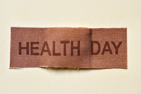 adhesive bandage: closeup of a fabric adhesive bandage with the text health day, on an off-white background