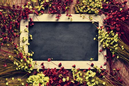 petites fleurs: un tableau noir à ossature en bois blanc entouré de rouge et jaune petites fleurs