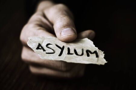 rights: closeup of the hand of a young man with a piece of paper with the word asylum, with a dramatic effect