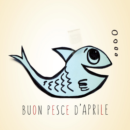 buon: a blue handmade paper fish attached with adhesive tape and the text buon pesce d aprile, happy april fools day in italian