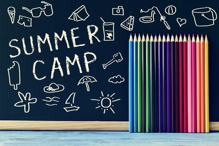 enkele tekeningen van de zomer spullen en de tekst zomerkamp geschreven op een schoolbord en enkele gekleurde potloden van verschillende kleuren, op een blauwe rustieke houten tafel