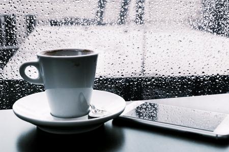 close-up van een kopje koffie en een smartphone op een tafel, terwijl er buiten regent