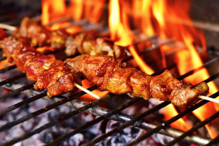 barbecue grill: closeup of some meat skewers being grilled in a barbecue
