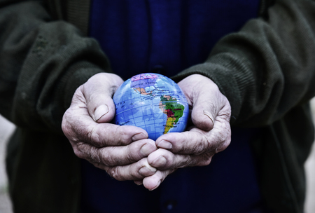 closeup of an old caucasian man with a world globe in his hands, with a dramatic effect Stock Photo