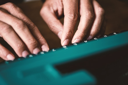 closeup of the hands of a young man typing in an old blue typewriter