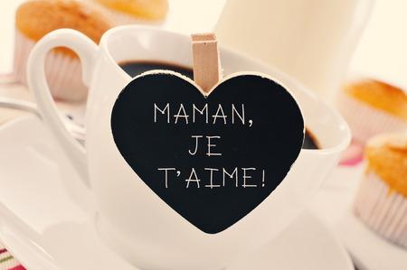 het vonnis Maman je t aime, ik hou van je moeder geschreven in het Frans in een hartvormig bord geplaatst in een kopje koffie