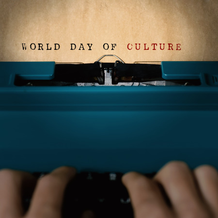 essayist: the text world day of culture written in a yellowish paper with a blue retro typewriter