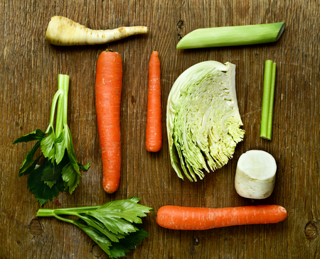 parsnips: high-angle shot of some pieces of different raw vegetables, such as carrots, parsnips, turnips, cabbage and celery, on a rustic wooden table Stock Photo