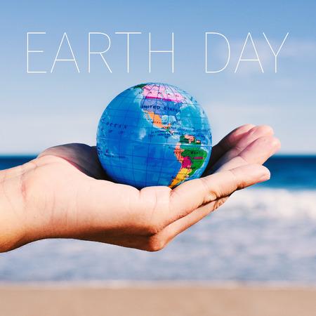 erde: Nahaufnahme eines jungen kaukasischen Mann mit einer Weltkugel in der Hand und dem Text Tag der Erde Lizenzfreie Bilder