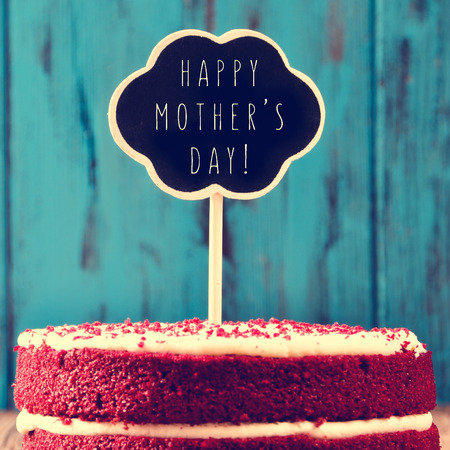 Closeup d'un gâteau de velours rouge surmonté d'un tableau en forme de bulle de pensée avec le texte fête des mères heureuses, contre un fond bleu en bois rustique