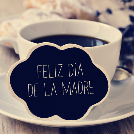 the sentence feliz dia de la madre, happy mothers day in spanish in a blackboard in the shape of a thought bubble placed in a cup of coffee Stock Photo