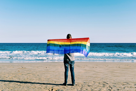 a young caucasian man seen from behind extending a rainbow flag in front of the ocean