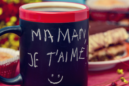 i t: the sentence maman je t aime, I love you mom in french handwritten with chalk in a black mug with coffee