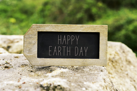 mother earth: closeup of a label-shaped chalkboard with the text happy earth day on a rock with a landscape in the background