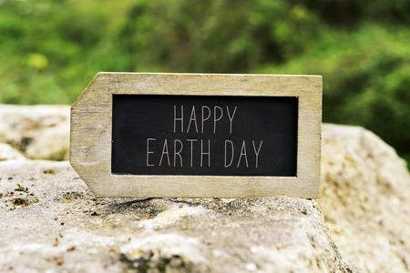 planeta tierra feliz: Primer plano de una pizarra en forma de etiqueta con el día de la tierra feliz de texto en una roca con un paisaje de fondo