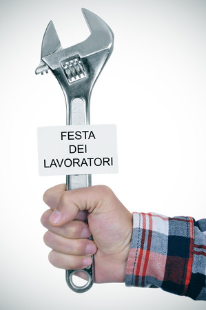 labour: closeup of the hand of a young caucasian worker man with an adjustable wrench and a signboard with the text festa dei lavoratori, labour day in italian Stock Photo