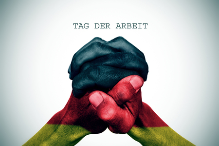 joblessness: man hand patterned with the flag of Germany put together and the text tag der arbrit, labour day in German, with a slight vignette added