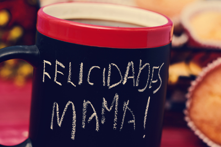 mama: the sentence felicidades mama, congratulations mom in Spanish, handwritten with chalk in a black mug with coffee
