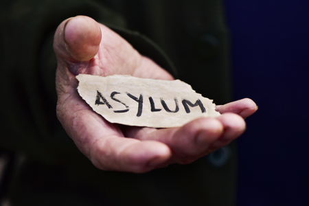 illegal immigrant: closeup of the hand of an old man with a piece of paper with the word asylum, with a dramatic effect