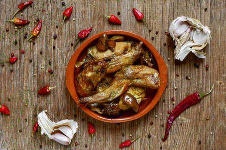 high-angle shot of an earthenware plate with conejo al ajillo, a typical spanish recipe of rabbit with garlic and parsley, on a rustic wooden table Imagens